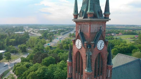 Thumbnail for Church in Small City Among Pastures. Drone Footage. Red Church Is Roman Catholic Church