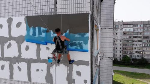 Aerial, Industrial Climber for Insulated Facades Putty Cement on Fiberglass Mesh