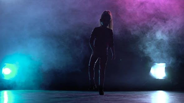 Thumbnail for Girl Stands in a Dark Studio and Raises Her Leg Up. Multicolor Smoke Background. Silhouette