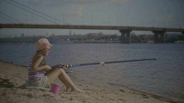 Thumbnail for Little Girl with Fishing Rod Sitting on River Bank