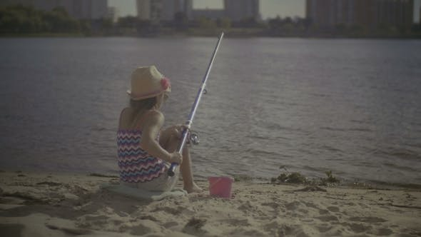 Beautiful Little Girl Fishing with Spinning Rod