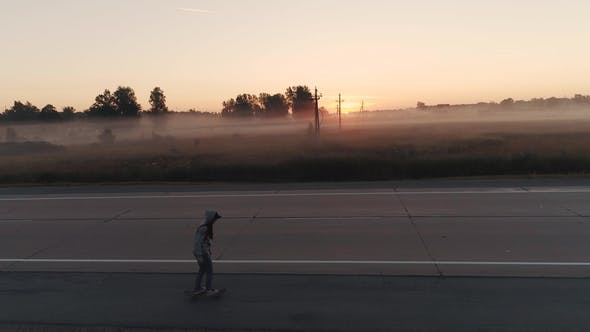 Thumbnail for A Teenage Girl Skates on a Skateboard Along a Deserted Road Outside the City at Dawn