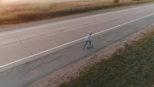 Thumbnail for Aerial. a Teenage Girl Skates on a Skateboard Along a Deserted Road Outside the City at Dawn. Young