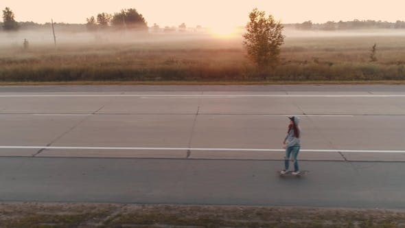 Thumbnail for Aerial. a Young Girl Is Riding on a Skateboard Along a Deserted Highway at Dawn