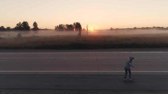 Thumbnail for Girl Is Riding on a Skateboard Along an Empty Highway at Sunset
