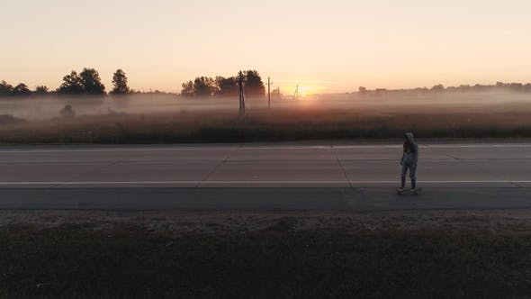 Thumbnail for a Young Girl Is Riding on a Skateboard Along a Deserted Highway at Dawn