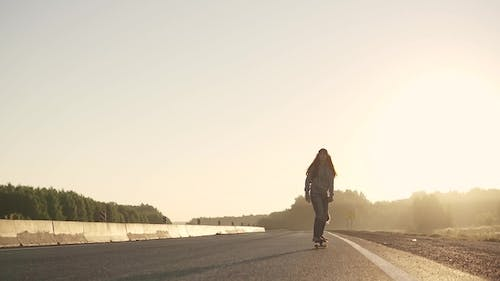 Girl Skates on a Skateboard on a Deserted Highway at Sunset Youth Subculture