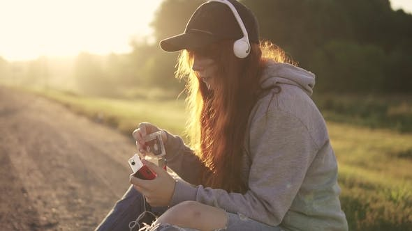 Thumbnail for Girl Hipster Inserts a Cassette Into a Cassette Player and Listen To Music on Headphones at Sunset
