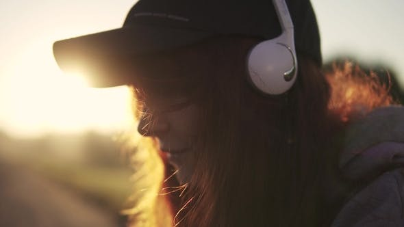 Thumbnail for Portrait of a Red-haired Girl in Headphones. Girl Listening To Music on Headphones at Sunset