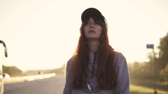 Thumbnail for Portrait of a Girl Hipsters at Sunset. Red-haired Girl Wearing Headphones and a Cap