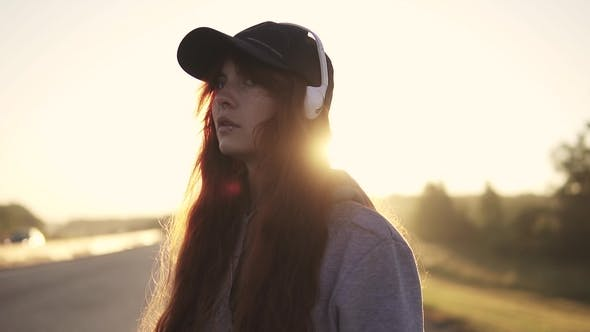 Thumbnail for Portret Red-haired Girl in the Rays of the Rising Sun. Hair Fluttering in the Wind. Teenager Listens