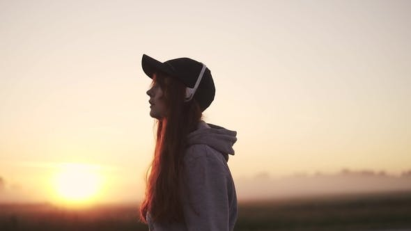 Thumbnail for Silhouette of a Girl in Headphones Against the Setting Sun in Nature