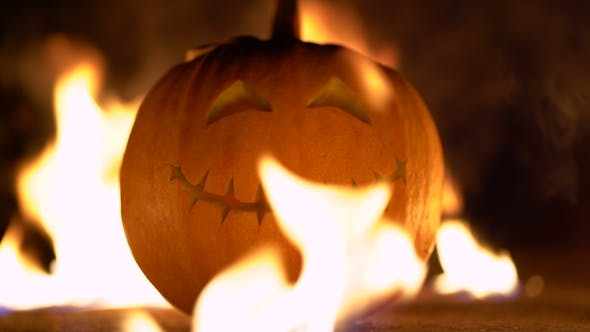 Thumbnail for Smiling Happy Carved Halloween Pumpkin Against of Fiery Explosion Background. Glowing Face Trick or