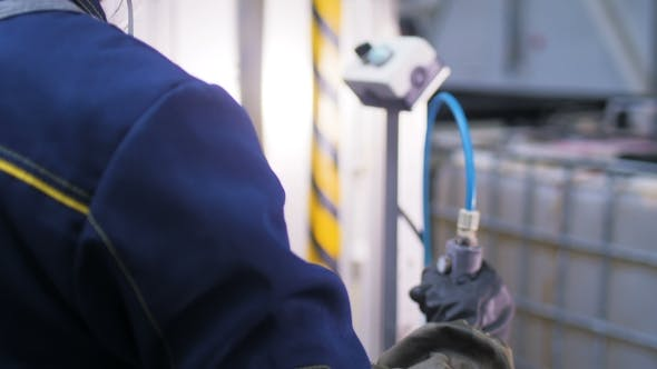 Thumbnail for Backside View Worker Twists Screws on Accumulators on Conveyor