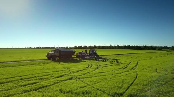 Thumbnail for Flycam Rises Above Agricultural Equipment Shows Vast Landscape