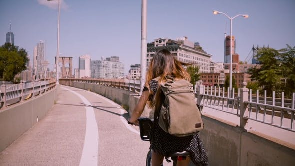 Thumbnail for Back View Happy Girl with Flying Dark Hair Riding a Bicycle Along a Separate Bike Lane in New York
