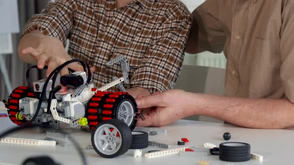 Thumbnail for Senior Man Helps His Grandson To Assemble Toy Vehicle