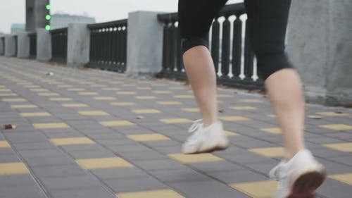 Running woman. Female jogging fast along city bank