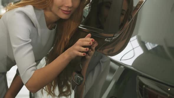 Cover Image for Cropped Close Up of a Woman Checking Out Car Paint on a New Automobile at the Dealership