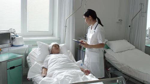 Female Doctor Talking with Patient during Morning Rounds