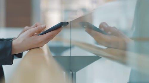 Nahaufnahme weiblicher Hände, die ein Mobiltelefon halten. Eine Frau benutzt ein Smartphone mit einem Touchscreen auf einem
