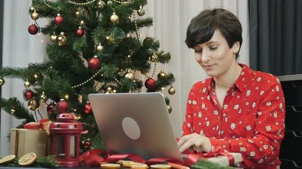 Thumbnail for Frau arbeitet am Laptop in der Nähe von geschmücktem Weihnachtsbaum
