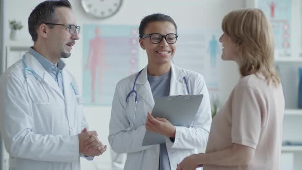 Thumbnail for Cheerful Multiethnic Doctors Speaking with Female Patient