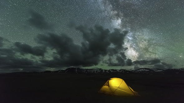 Thumbnail for Milky Way Is Moving Across Starry Sky with Clouds Over Yellow Glowing Tent