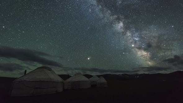 Thumbnail for Milky Way Is Moving Across Starry Sky with Clouds Over Yurt Camp