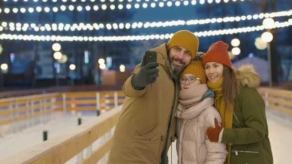 Fröhliche Familie nimmt Selfie auf Eisbahn