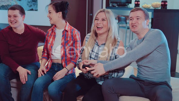 Group of Laughing Male and Female Friends Playing Video Games with Wireless Controllers