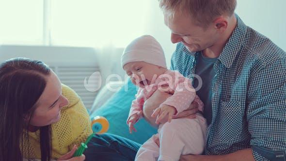 Happy Parents Kiss a Newborn Baby