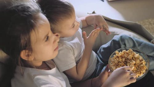 Happy Family Brother and Sister Watching Tv with Popcorn Bowl at Home