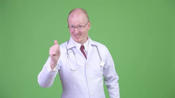 Thumbnail for Happy Mature Bald Man Doctor Thinking While Giving Thumbs Up