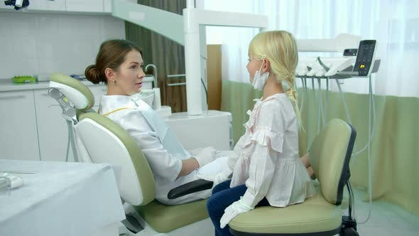 Cover Image for Dentist Talks with Little Girl in Cabinet