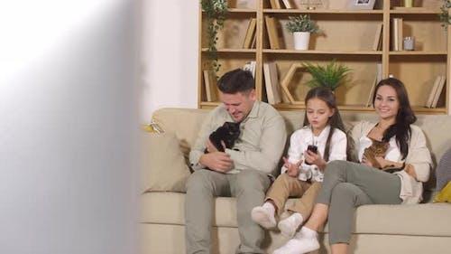 Happy Family regarder la télévision et caresser les chats sur le canapé à la maison