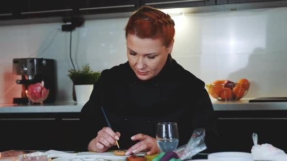 Frau, die bemalte Zuckerkekse in der Küche zu Hause