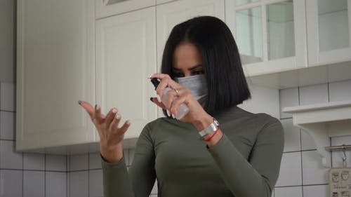 Black woman use sanitizing spray
