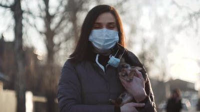 Woman in Protective Face Mask with Small Dog Wearing Medical Mask Too