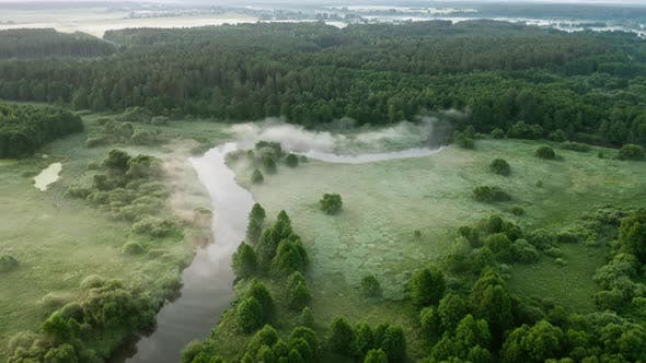 Thumbnail for Aerial view winding river flows through green meadows and forest. Clouds of fog over water surface