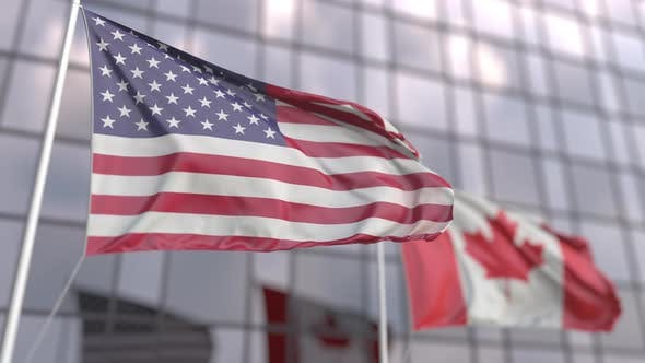 Waving Flags of the USA and Canada in Front of a Skyscraper