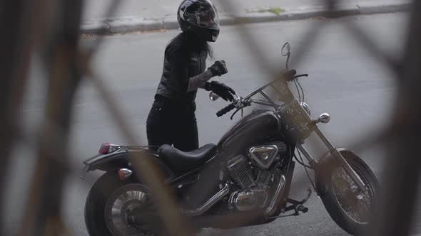Thumbnail for Pretty Girl in Leather Vest Rides a Motorcycle and Parks Near the Building
