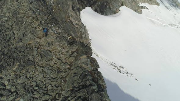 Thumbnail for Hiker Man Is Hiking and Descending Near Cliff in Snowy Mountains of Norway. Aerial View