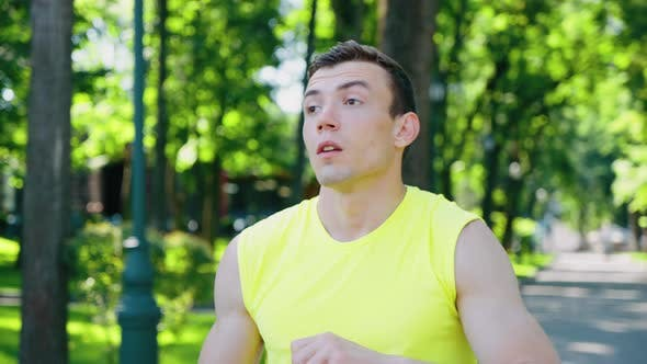 Man Drinking Water After Workout in Park