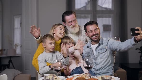 Thumbnail for Charming Laughing Family which Sitting at the Dinner Table and Making Selfie