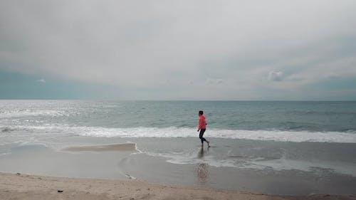 Slim female is walking along sea water waves on sandy beach
