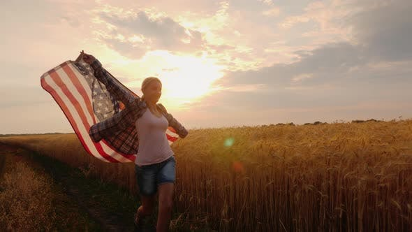 Thumbnail for A Woman with a USA Flag Runs Across a Wheat Field in the Sun's Rays at Sunset