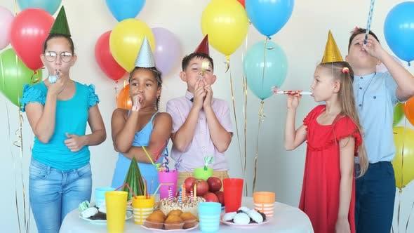 Kinder Blow Party Hörner feiern Geburtstag am Tisch
