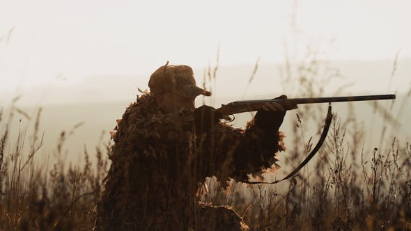 Thumbnail for Hunter in hunting equipment lies in wait in the field