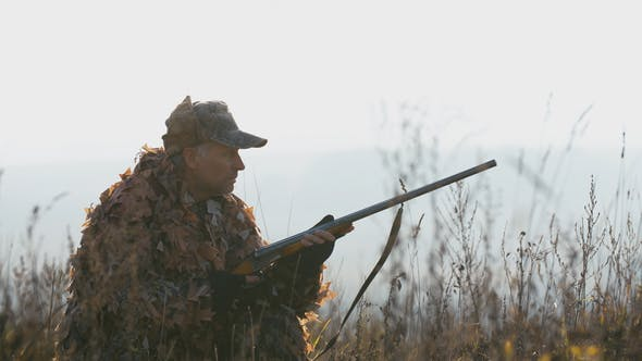 Cover Image for A Man in Hunting Equipment in Sunset Light Find the Target and Aim